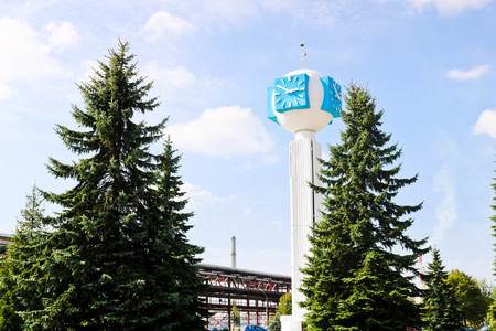 Unusual clock on a background of a white-blue sky. A clock in the form of a molecule, an atom. On chemical production, a watch-column, a clock tower in a spruce forest. Backdrop of chemical pipelines. Stock Photo