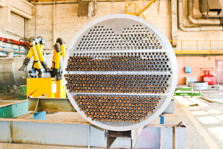 Production of a large tube bundle for a shell-and-tube heat exchanger in an industrial production room of a shop with equipment at an oil refinery, petrochemical, chemical plant, enterprise. Stock Photo