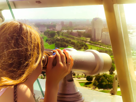 A beautiful girl looks at the landscape, a panorama of the city in the observation room, a pair of binoculars, a telescope with a bill acceptor on an observation deck in the open air. Stock Photo