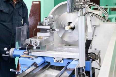 Un trabajador masculino trabaja en un torno de cerrajería de hierro de metal más grande, equipo para reparaciones, trabajo en metal en un taller en una planta metalúrgica en una producción de reparación.