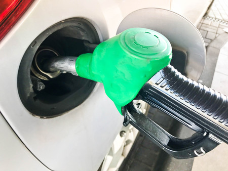 Green filling pistol stuck in the gas tank of a car at a gas station. The process of filling the car with fuel, gasoline, diesel.