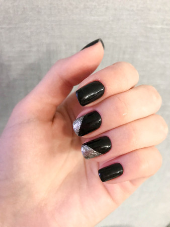 Beautiful female hand with thin fingers and black manicure with gel polish with silver sparkles on the nails.