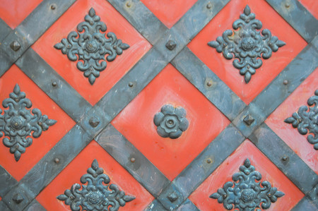 Texture of an old ancient medieval red antique sturdy iron metal door with rivets and nails patterns. The background.