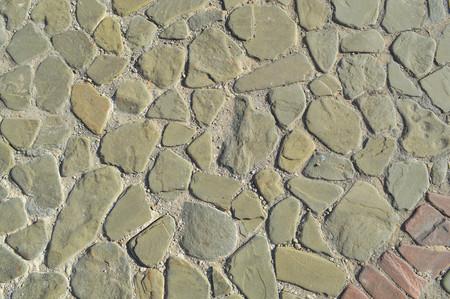 La textura del camino de piedra, pavimento, paredes de grandes piedras fuertes redondas medievales grises, adoquines. El fondo.