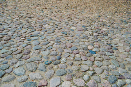 The texture of the stone road, pavement, walls of large gray old medieval round strong stones, cobblestones. The background.
