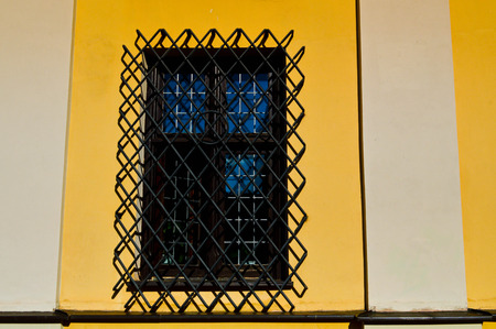 A large rectangular window of a yellow stone building closed by a large black iron grate. The background. 版權商用圖片