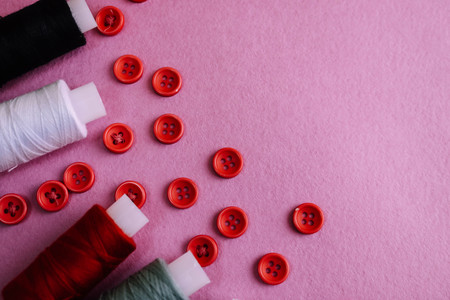 Beautiful texture with lots of round red buttons for sewing, needlework and skeins of spools of thread. Copy space. Flat lay. Pink, purple background. 写真素材