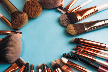 A frame from a set of beautiful different soft makeup brushes from natural lint for targeting beauty and applying a tonal foundation in a stand and copy space on a blue background. Stock fotó