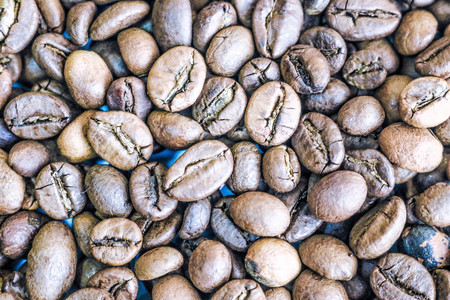Beautiful texture of freshly roasted selected delicious rich brown natural fragrant coffee tree grains, Arabica coffee beans, Robusta. Flat lay and copy space. The background. Stock Photo