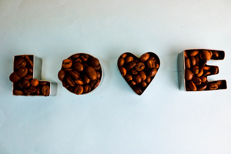 Beautiful texture with the word love for valentines day inscription made from roasted selected brown natural aromatic Arabica coffee beans, robusta Copy space, flat lay, blue background.