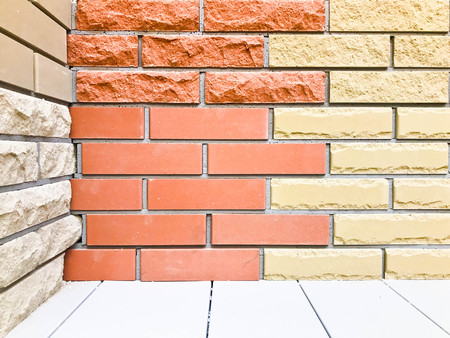 Beautiful texture of a decorative wall and floor from two-tone building brown red and yellow textured relief brick with seams. The background.