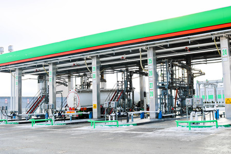 Large green industrial gas station for refueling vehicles, trucks and tanks with fuel, gasoline and diesel in the winter. Stock Photo