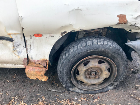 Old white rusty broken car of the carcass with lowered punctured wheels with scratches corrosion and a torn-off bumper with dents and scratches thrown on the road. Auto junk. Stock Photo