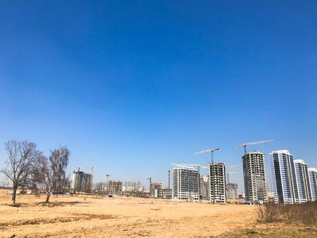 Bauen mit Hilfe von Baukränen aus hochbewehrtem Beton, Platten, Gussrahmen, Blockhäusern, Gebäuden, Wolkenkratzern, Neubauten auf dem Hintergrund von sandigem Land.