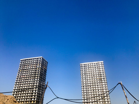 Two large high reinforced concrete, panel, monolithic-frame, frame-block houses, buildings, skyscrapers, new buildings with a glare of the sun in the windows against the blue sky. Imagens