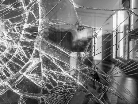The texture of the broken cracked thick fragile broken sharp glass, triplex with shiny small fragments. The background. Stock Photo