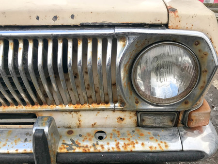 An old retro vintage hipster rusty oxidized chrome-plated metallic silver radiator grille and a round glass retro spotlight of an antiquan white white American car from the 60s, 70s, 80s, 90s, 2000s.