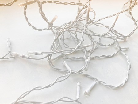 Twisted white wires of a garland in white rubber insulation with light bulbs on a white background. Stock fotó