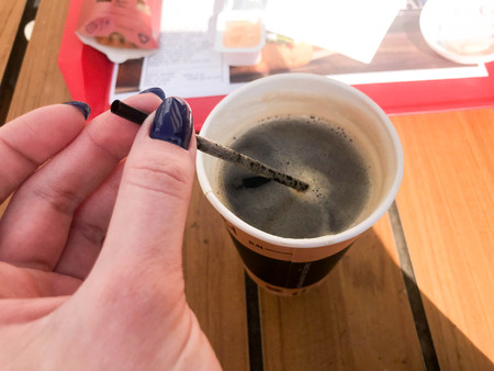 A woman holds with a beautiful manicure on her fingers a tube in a cup of fast black hot strong natural coffee from fast food in a paper glass.