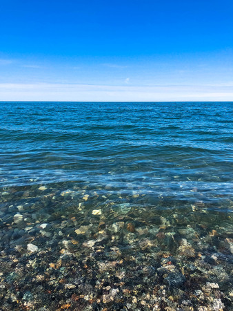 Beautiful multi-colored round stones on the sea, rivers, lakes, pond, ocean and boiling water with waves on the rocky beach of a tropical warm resort on the horizon and sky. Vertical view.