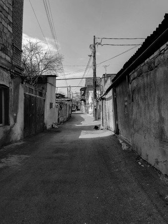 Narrow street, lane, tunnel with old houses, buildings on the sides in a poor area of the city, slums. Vertical photo.
