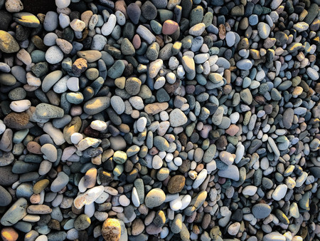 Texture of many multicolored beautiful round and oval smooth natural stones, pebbles. The background.