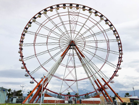 A large round beautiful Ferris wheel, a panoramic platform in a park on a tropical sea warm summer resort with palm trees against a blue sky.