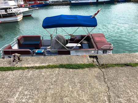 A small boat with a stretch canvas roof stands on the quay at the port on the water in the sea. 版權商用圖片
