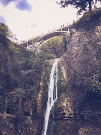 Beautiful mountain waterfall with a falling stream of water flowing from under a bridge on a cliff overgrown with trees and plants.