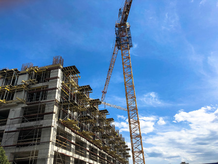 Construction of a monolithic frame house of concrete and gas silicate blocks with lots of scaffolding using a large crane against a blue sky. Stock Photo