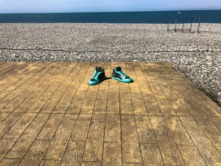 Green sports sneakers, shoes on a wooden platform on a sandy beach against the background of the sea.