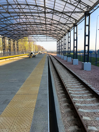 Modern railway station, train station with a transparent canopy for passengers and rails.