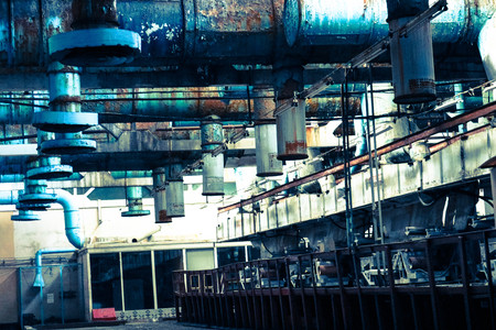 Old rusty peeling ceiling in a workshop at an industrial chemical petrochemical machine-building oil refinery with blue metal iron large pipes for inlet and exhaust ventilation.