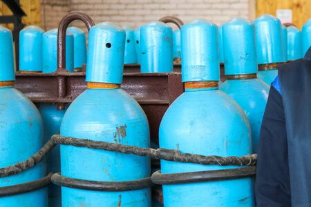 Large iron metal blue gas cylinders with oxygen, air, helium under excessive internal pressure to store compressed, liquefied and dissolved under pressure gases.