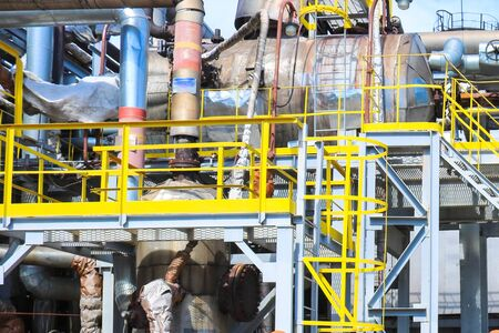 Iron metal industrial plant installations with stairs, fences and pipes, distillation columns at the oil refining chemical metallurgical construction plant.