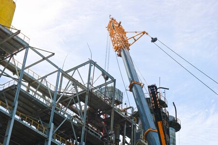 Construction and installation work with a powerful construction crane of a large new industrial oil refining petrochemical chemical plant with pipes, columns, railings, stairs and equipment.