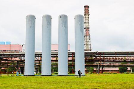 Large metal tanks of the column and high pipes at the industrial refinery petrochemical chemical plant.