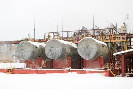 Large iron tanks, ladders and protective fencing pipes equipment and machine tools valves heat exchangers at a petroleum refining petrochemical chemical industrial plant. Stock Photo