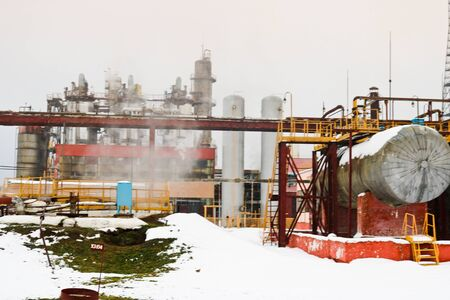 Large installation with equipment for heat exchangers with tanks and columns at an industrial refinery petrochemical chemical plant in the snow in winter.