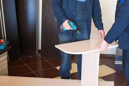 Un trabajador de hombre en ropa de trabajo que trabaja con un destornillador en sus manos está montando muebles. Reparación profesional en el apartamento.