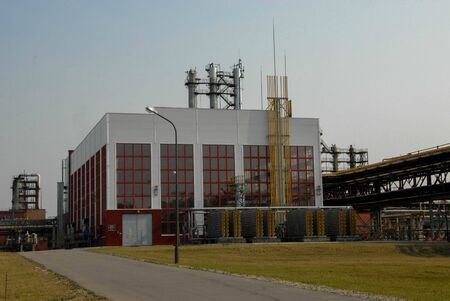 Large building with production equipment with pipes, pumps, compressors and distillation columns at a petroleum refining petrochemical chemical plant.