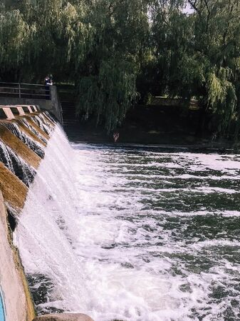 Beautiful waterfall, a small dam on an artificial pond river lake with falling fast water with splashes.