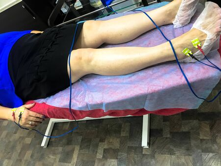 A person is given a bioimpedance medical analysis to diagnose body composition. Sensors are connected to the leg for medical analysis and patient care. Banco de Imagens