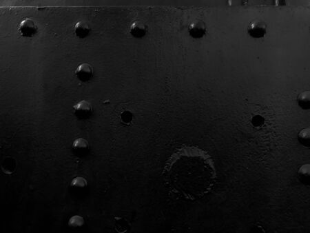 Black iron metal rough painted strong solid industrial wall with rivet holes and bolts. Background, texture.