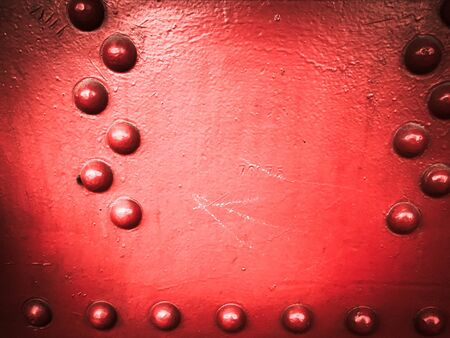 Red iron metal rough painted strong solid industrial wall with rivet holes and bolts. Background, texture.