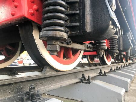 Large iron wheels of a red and black train standing on rails and suspension elements with springs of an old industrial steam locomotive.
