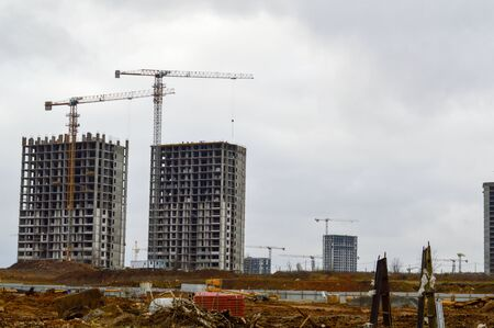 Construction of large modern monolithic frame houses, buildings using industrial construction equipment and large high cranes. Construction of the building in the new micro district of the city. Stock Photo