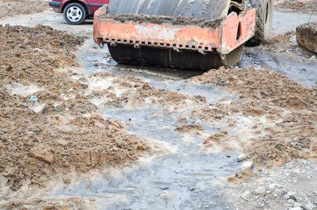 泥の中にアスファルト道路の建設のための大規模な強力な建設産業貨物スケートリンク。