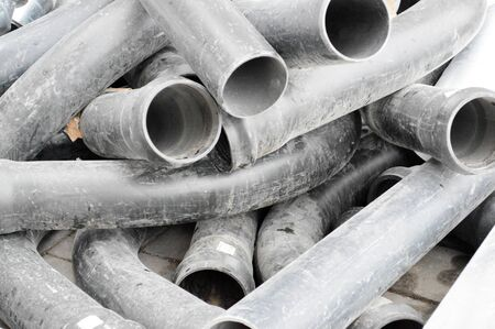 Large black plastic sewer plumbing pipes for the construction of water pipes or sewers at a construction site during the repair. Background, texture.