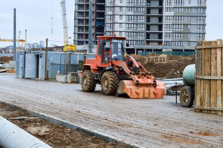 Big bright yellow powerful industrial heavy excavator tractor, bulldozer, specialized construction equipment for road repair during the construction of a new micro-district in a big city.